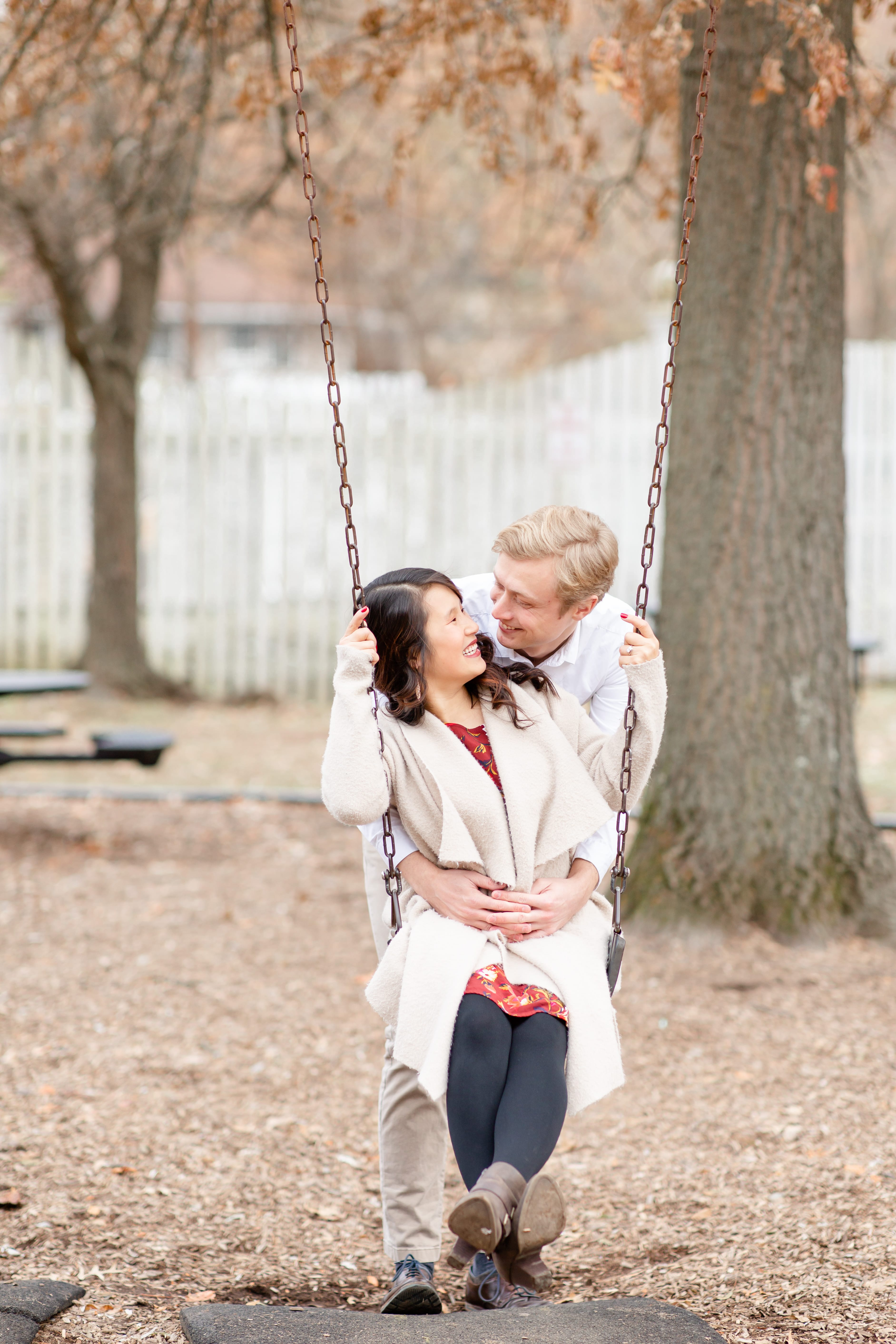 Engaged couple sitting on the swing at Talleyrand Park in Bellefonte