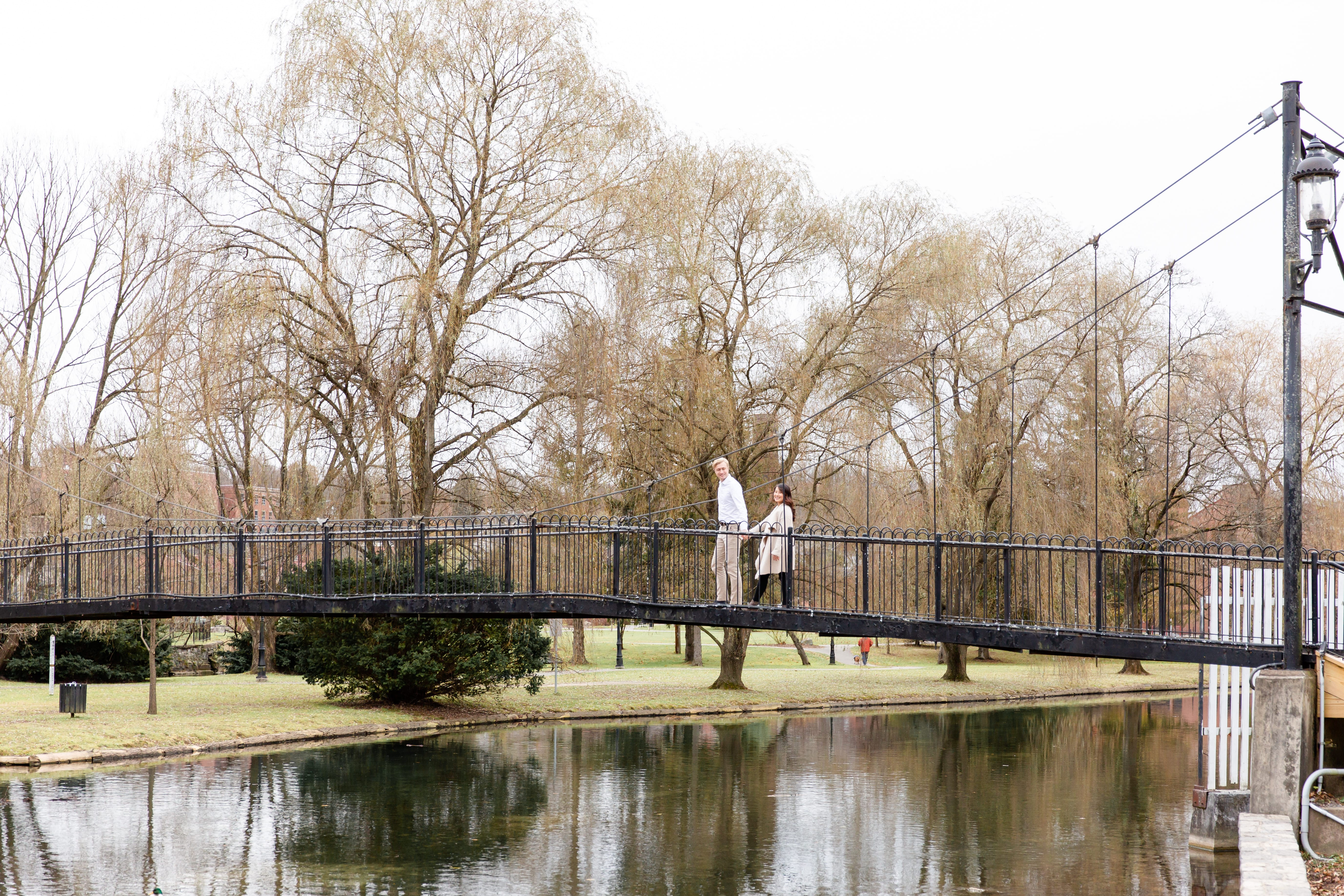 Engaged couple crossing the bridge at Talleyrand Park in Bellefonte