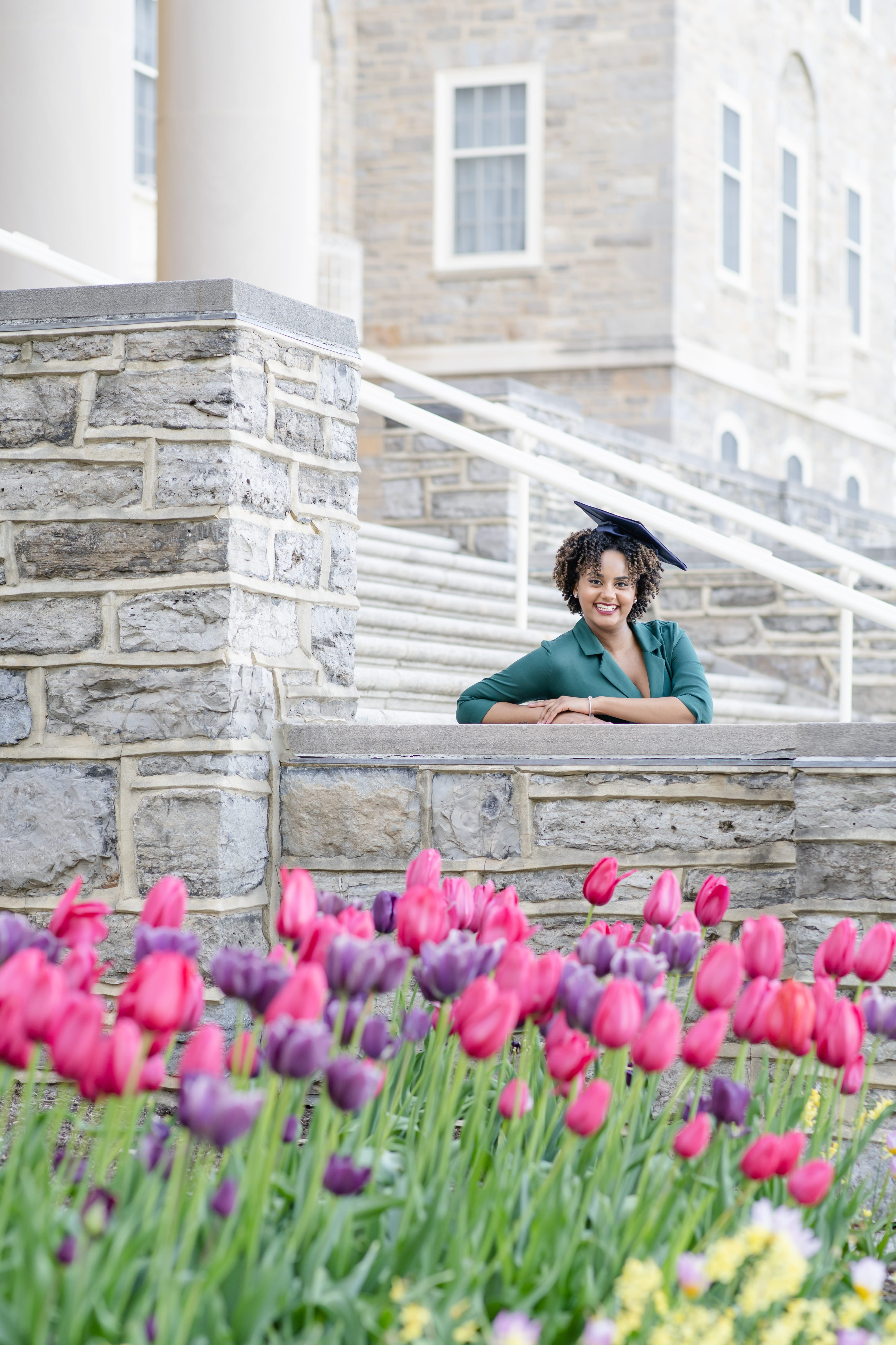 Class of 2020 Penn State graduate at Old Main with beautiful tulips during spring