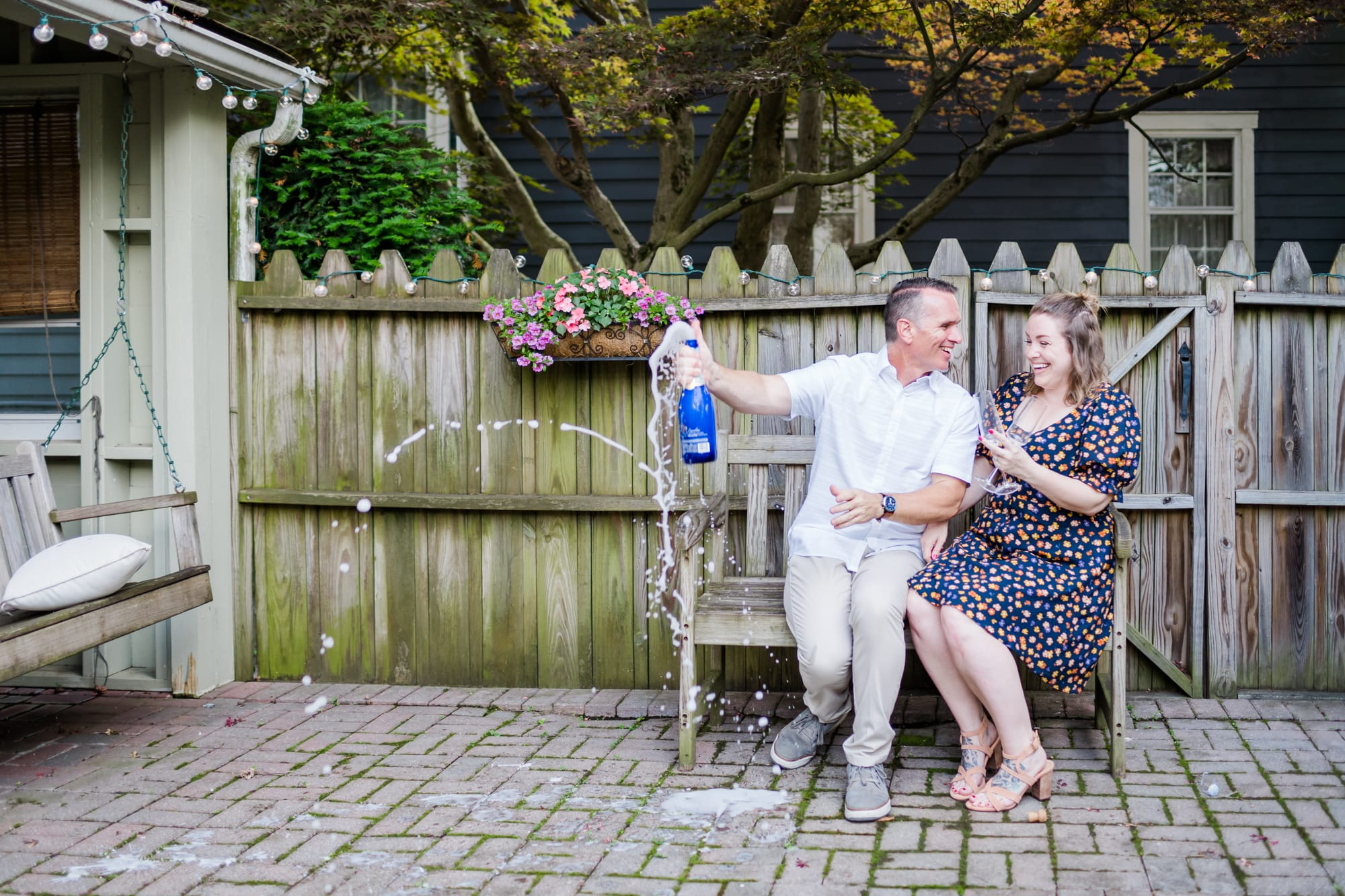 In-home lifestyle engagement photos with champagne pop