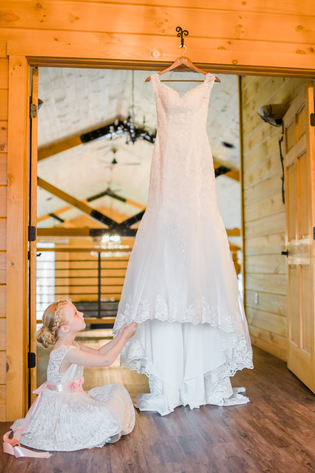 Flower girl gazing at the wedding dress at Rolling Rails Lodge