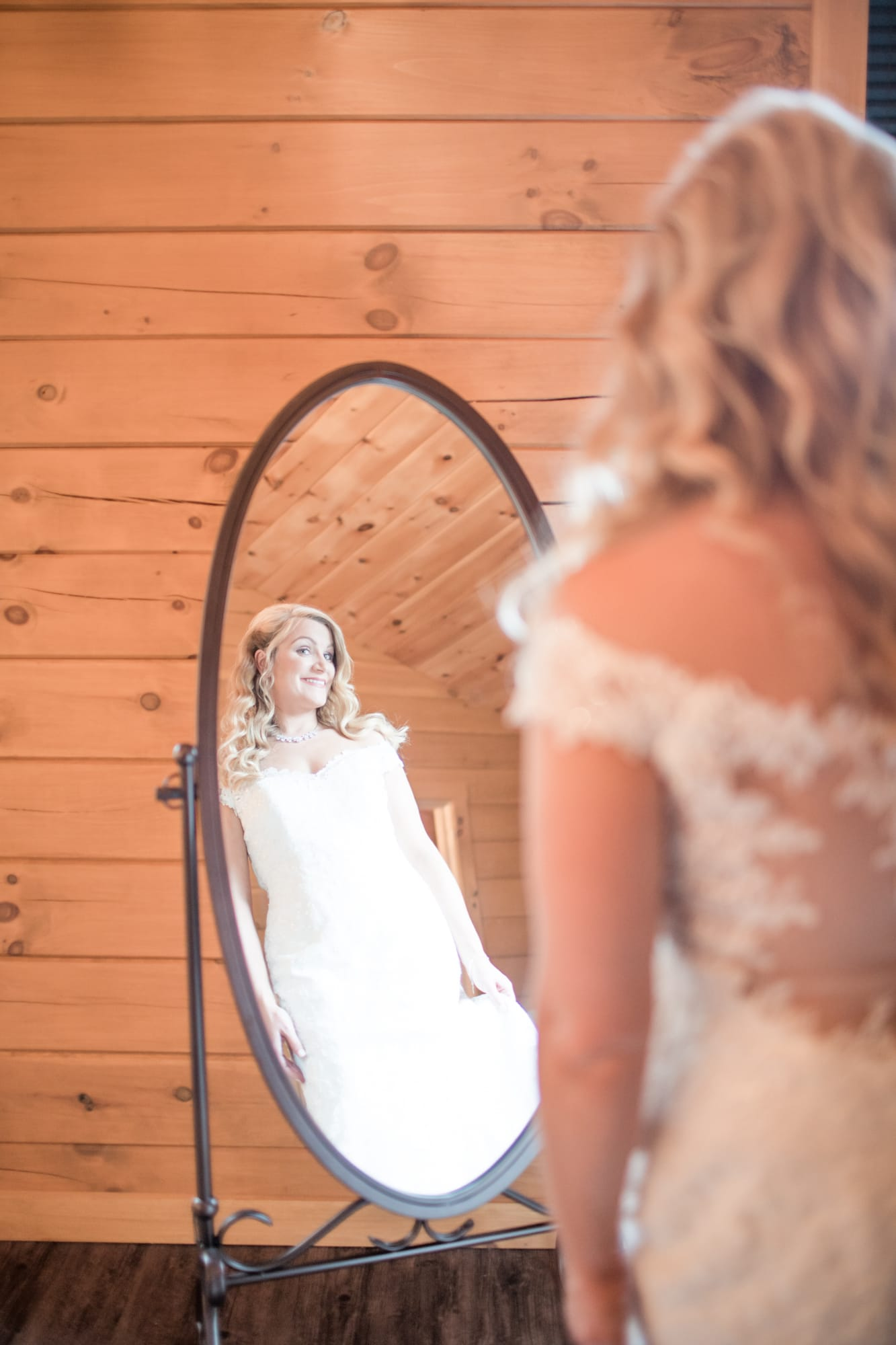 Bride admiring herself at Rolling Rails Lodge wedding